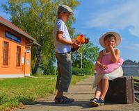 Adorable little girl and boy on a railway station, waiting for the train with vintage suitcase. Traveling, holiday and. Chilhood concept. Travel insurance royalty free stock photos