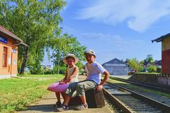Adorable little girl and boy on a railway station, waiting for the train with vintage suitcases. Traveling, holiday and chilhood c. Oncept. Travel insurance stock photos