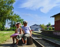 Adorable little girl and boy on a railway station, waiting for the train with vintage suitcases. Traveling, holiday and chilhood c royalty free stock photography