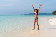 Adorable little girl in a bright bathing suit at beach during summer vacation. The young girl raises his hands up and rejoices. royalty free stock image