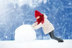 Adorable little girl building a snowman in beautiful winter park. Cute child playing in a snow. Winter activities for kids Royalty Free Stock Photos