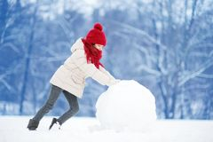 Adorable little girl building a snowman in beautiful winter park. Cute child playing in a snow. royalty free stock image