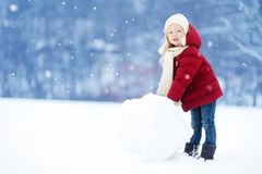 Adorable little girl building a snowman in beautiful winter park. Cute child playing in a snow. Winter activities for kids Stock Photo