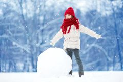 Adorable little girl building a snowman in beautiful winter park. Cute child playing in a snow. Winter activities for kids Stock Image