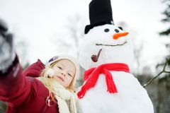 Adorable little girl building a snowman in beautiful winter park. Cute child playing in a snow. Winter activities for kids Stock Photos