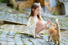 Adorable little girl and a cat. Adorable little girl met a cat while walking narrow streets ot typical italian town Stock Image