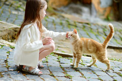 Adorable little girl and a cat. Adorable little girl met a cat while walking narrow streets ot typical italian town Stock Photo
