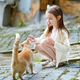 Adorable little girl and a cat. Adorable little girl met a cat while walking narrow streets ot typical italian town Stock Images