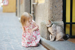 Adorable little girl and a cat outdoors Royalty Free Stock Images