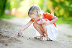 Adorable little girl catching little babyfrogs Royalty Free Stock Image