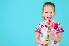Adorable little girl with cheeky smile and face expression holding bouquet of pink gerbera daisies. Happy Mother`s Day. Adorable little girl with cheeky smile Stock Photo