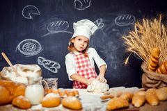 Adorable little girl in chef hat making dough. Wonderful content little girl in checkered apron and hat of chef standing at table and making bread dough looking stock image