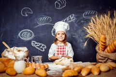 Adorable little girl in chef hat making dough. Wonderful content little girl in checkered apron and hat of chef standing at table and making bread dough looking royalty free stock photography
