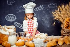 Adorable little girl in chef hat making dough. Wonderful content little girl in checkered apron and hat of chef standing at table and making bread dough looking stock photo