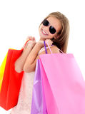 Adorable little girl child in sunglasses holding shopping colorful paper bags. Isolated on a white Royalty Free Stock Photo