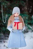 Adorable little girl with christmas box gift in Royalty Free Stock Image