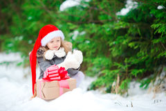 Adorable little girl with Christmas box gift in winter outdoors on Xmas eve. Cute little girl with christmas box gift in winter day Stock Images