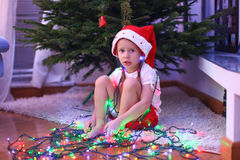 Adorable little girl in chritmas hat sitting under Royalty Free Stock Images
