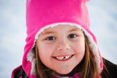 Adorable little girl close up in snow. Close up of cute young girl in pink toboggan smiling Royalty Free Stock Photography