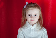 Adorable little girl - closeup portrait. Littlebit emootions from girl on red background Stock Image