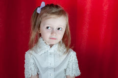 Adorable little girl - closeup portrait. Littlebit emootions from girl on red background Stock Photography