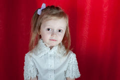 Adorable little girl - closeup portrait. Littlebit emootions from girl on red background Stock Photos
