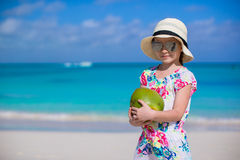 Adorable little girl with coconut at white beach during summer vacation Stock Image