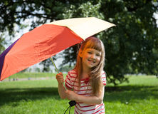 Adorable little girl with colored umbrella. Outdoors Stock Photo