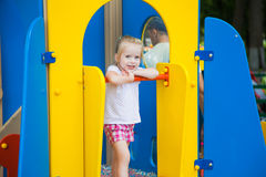Adorable little girl on a colorful playground Stock Images