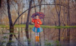Little girl in gumboots in puddle. Adorable little girl in colorful skirt and gumboots standing with umbrella in big puddle in woods Stock Image