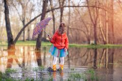 Little girl in gumboots in puddle Stock Images