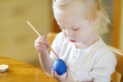 Adorable little girl coloring an Easter egg Royalty Free Stock Images