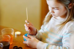 Adorable little girl coloring an Easter egg using wax Stock Image
