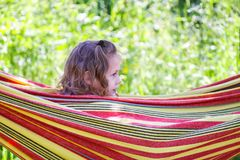 Adorable little girl with curly hair in hammock on summer nature background in countryside. royalty free stock images