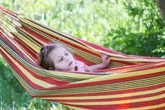 Adorable little girl with curly hair in striped hammock on summer nature background in countryside. stock photos