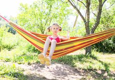 Little girl with curly hair in colorful striped hammock on summer nature background in countryside royalty free stock photography