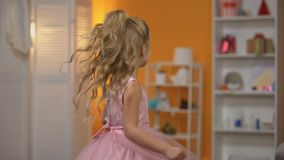 Adorable little girl dancing in pink dress, pretending to be princess, happiness stock video