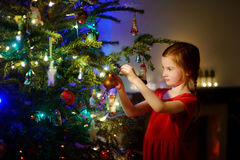 Adorable little girl decorating a Christmas tree. With colorful glass baubles at home Stock Photography