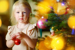 Adorable little girl decorating a Christmas tree with colorful glass baubles Stock Photography