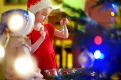 Adorable little girl decorating a Christmas tree Stock Image