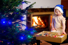 Adorable little girl decorating a Christmas tree Royalty Free Stock Photos