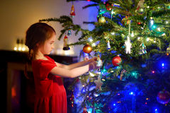 Adorable little girl decorating a Christmas tree. With colorful glass baubles at home Stock Image