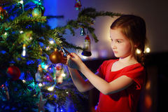 Adorable little girl decorating a Christmas tree Stock Photos