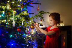 Adorable little girl decorating a Christmas tree Royalty Free Stock Images
