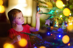 Adorable little girl decorating a Christmas tree. With colorful glass baubles at home Royalty Free Stock Photography