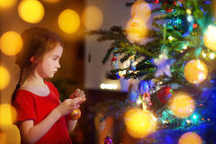 Adorable little girl decorating a Christmas tree Royalty Free Stock Photo