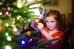 Adorable little girl decorating a Christmas tree Royalty Free Stock Image
