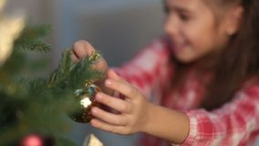 Girl hanging decorative toy ball on Christmas tree stock footage