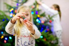 Adorable little girl decorating the Christmas tree with colorful glass baubles. Trimming the Christmas tree. Royalty Free Stock Photo