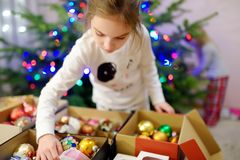 Adorable little girl decorating the Christmas tree with colorful glass baubles. Trimming the Christmas tree. Stock Images